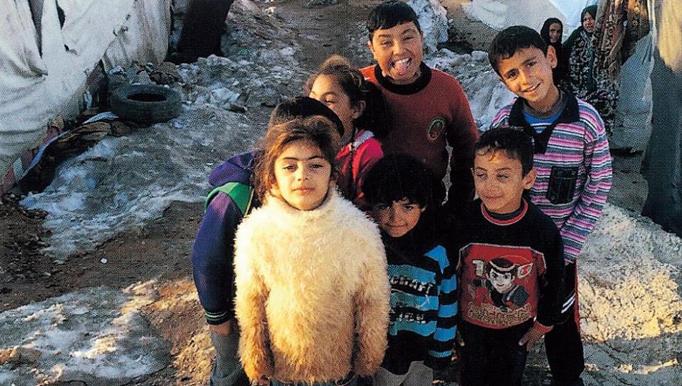 敘利亞難民兒童在黎巴嫩貝卡谷地臨時搭建的難民帳篷前。 照片取自《請帶我穿越這片海洋》,漫遊者文化提供