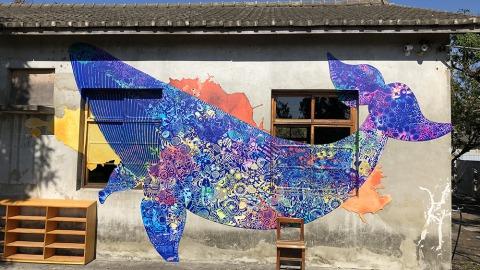 海灣繪本館主建物外牆上巨幅壯觀的大翅鯨,出自藝術家盧政憲之手。